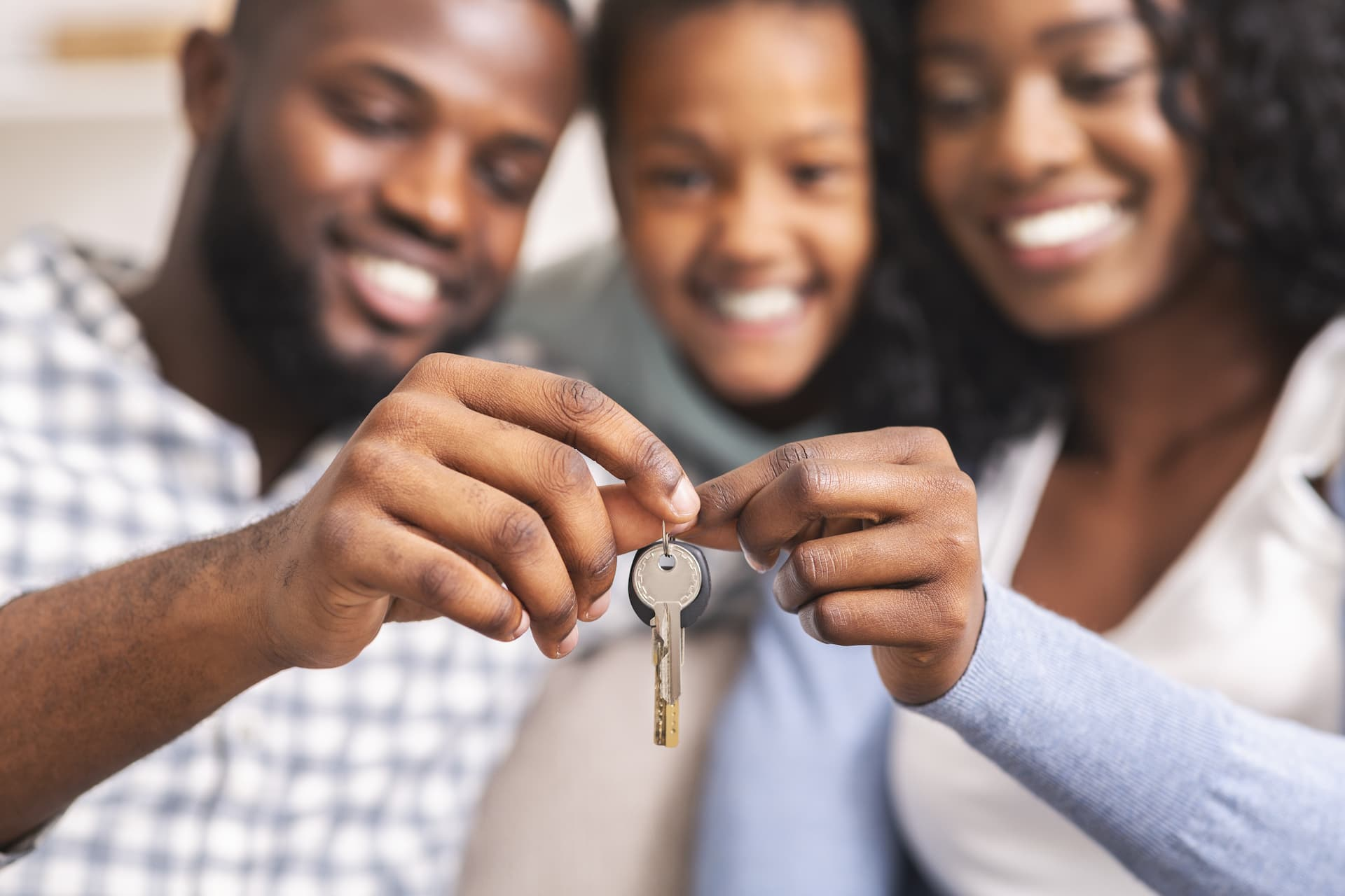 A young family holding the key to their new home at Watercolour Westport.