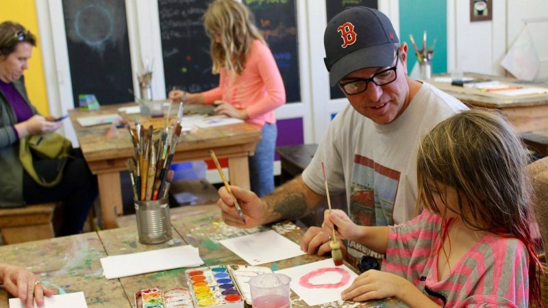 An image of a father wearing a Boston Red Sox baseball hat holding a paint brush, sitting next to his daughter who is painting something in an art studio.