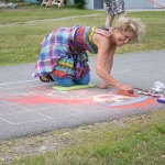 A woman wearing bright colors and kneeling on the pavement is using chalk to paint a portrait on the ground. She is smiling and kneeling on a foam pad while she draws in a large grid the beginnings of a face.