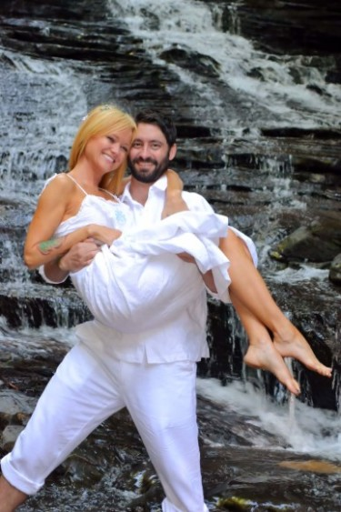 happy couple celebrates cheap elopement packages at a waterfall