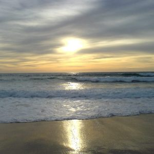 Sonnenuntergang am Meer, das gehende Wasser und der Strand in der Abendsonne