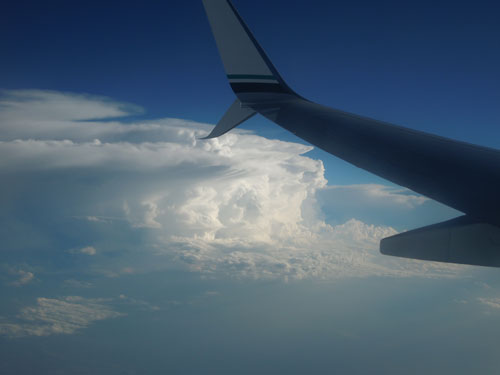 Taken from the sky and shows storm clouds and the wing of a jet.