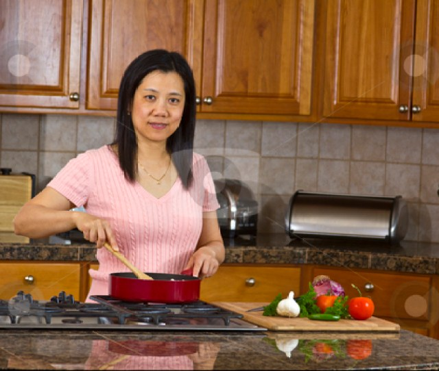 Asian Mom Cooking At Home Stock Photo
