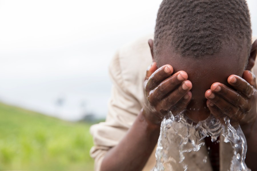 Young boy in Enariboo, Kenya, washes his face with clean, safe water for the first time.