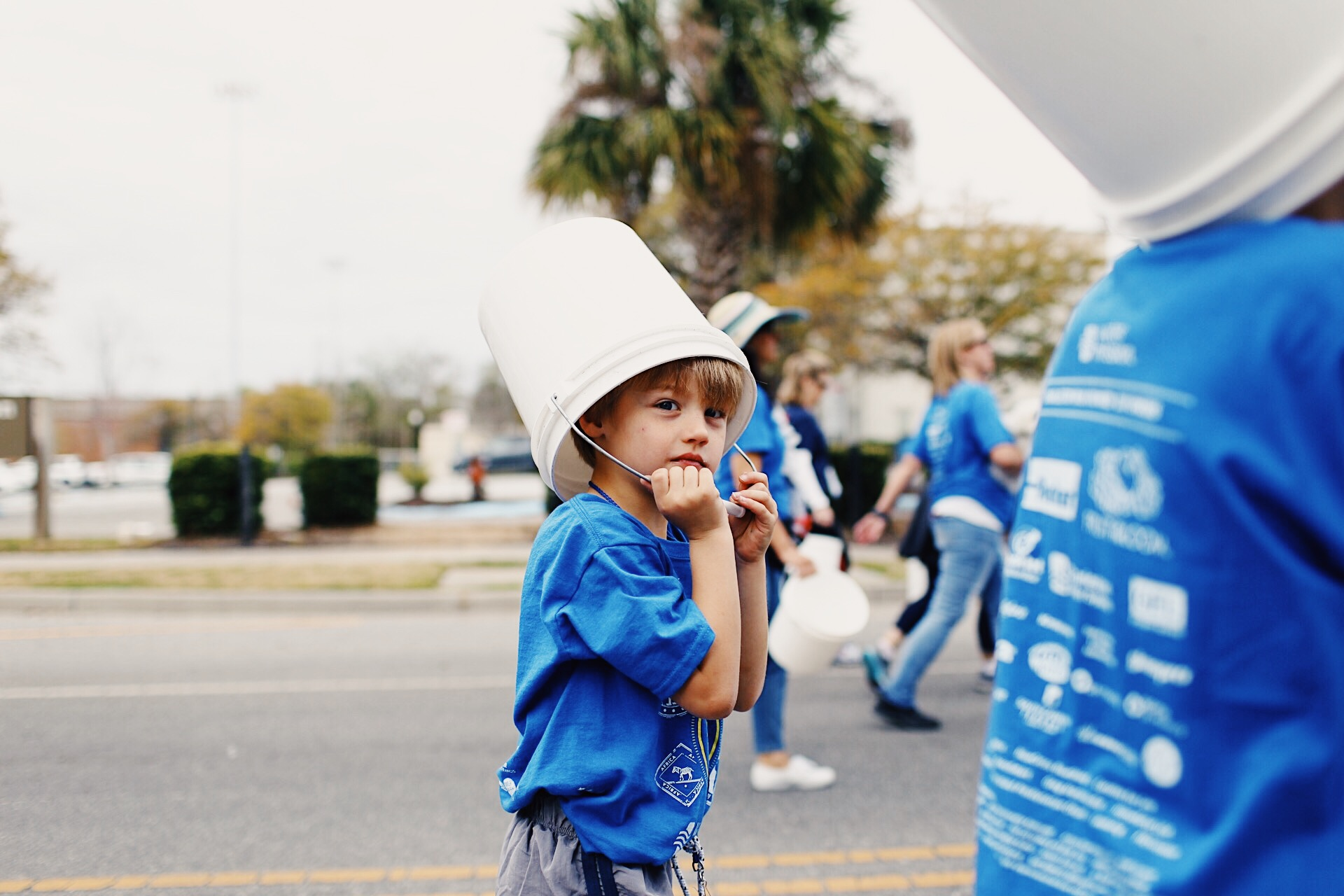 A young boy walks with his bucket on his head.