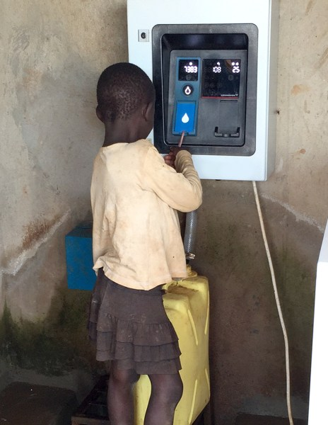 A young girl fills up her water bucket at an AQ Tap.