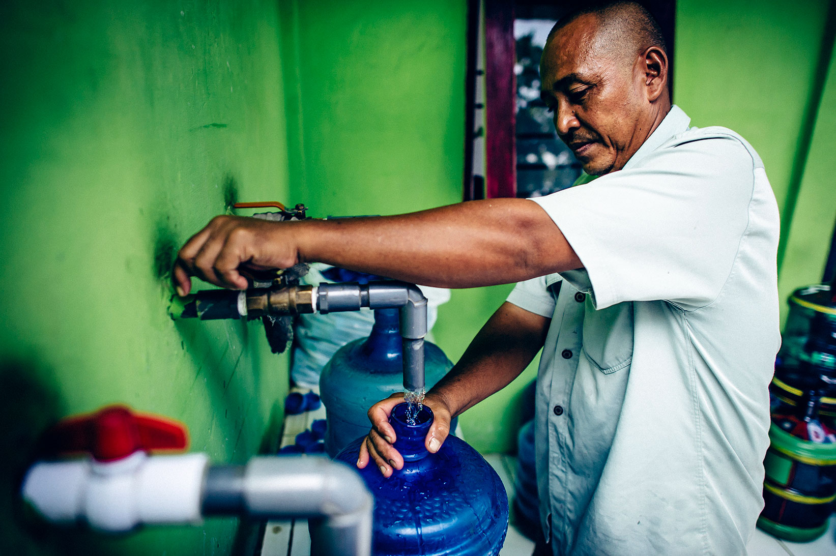 The system operator fills a jug with safe water.
