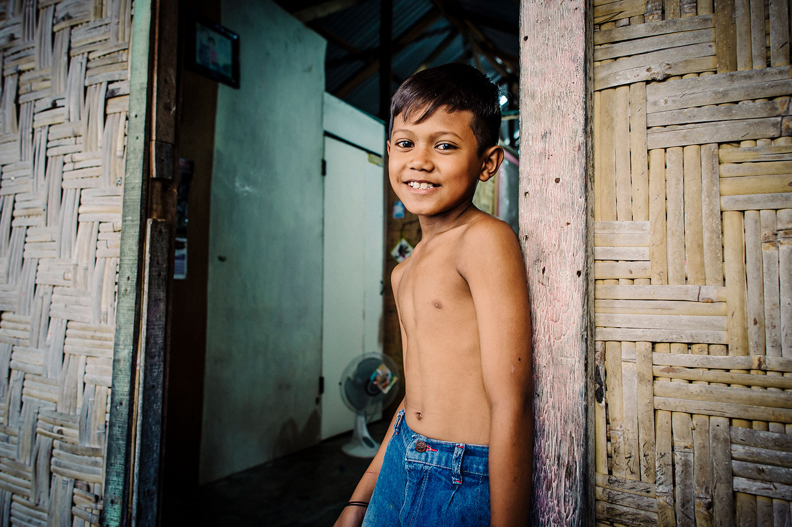 A young boy smiles at his home as he receives safe water.