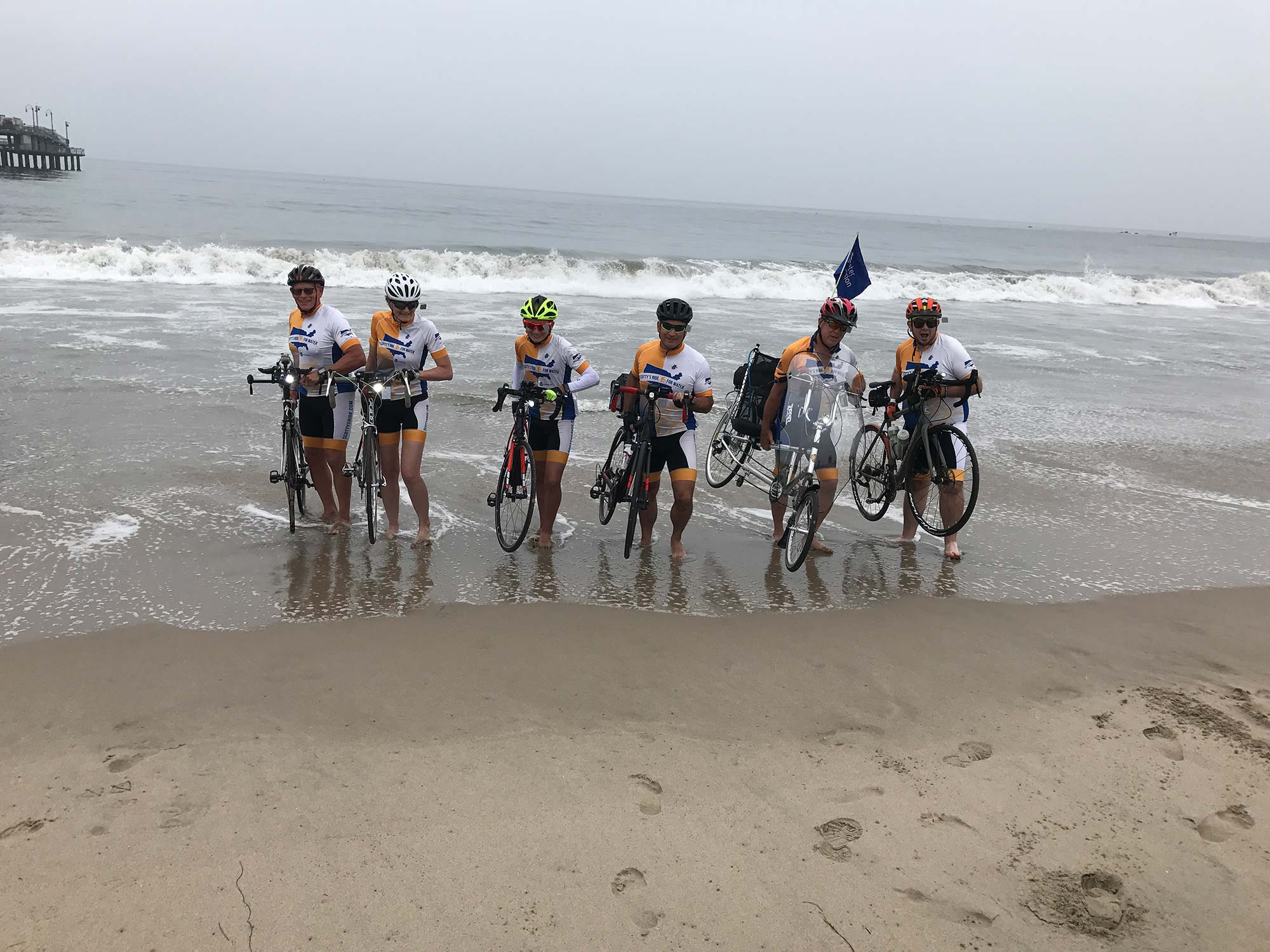The Scotty's Ride team dips their bike tires in the pacific ocean before heading East.