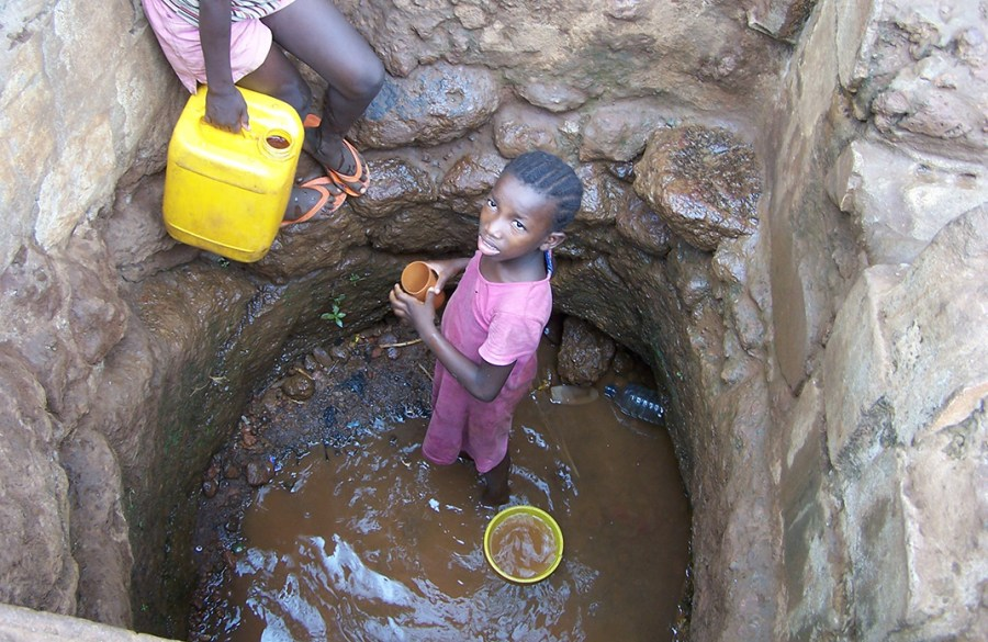 A young girl in Sierra Leone retrieves water from a well.