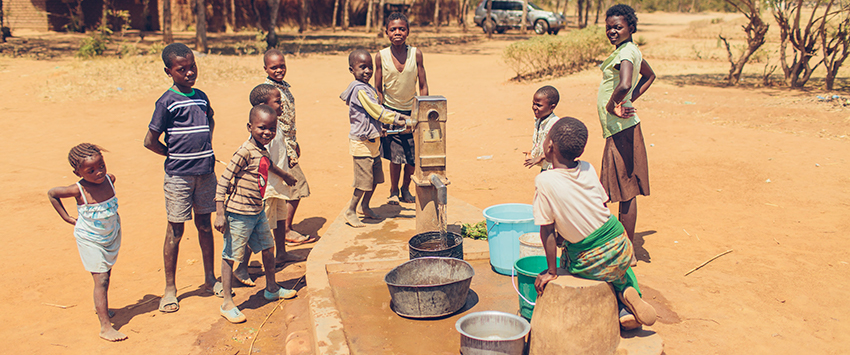 Children draw safe water from their community's tap in Malawi.
