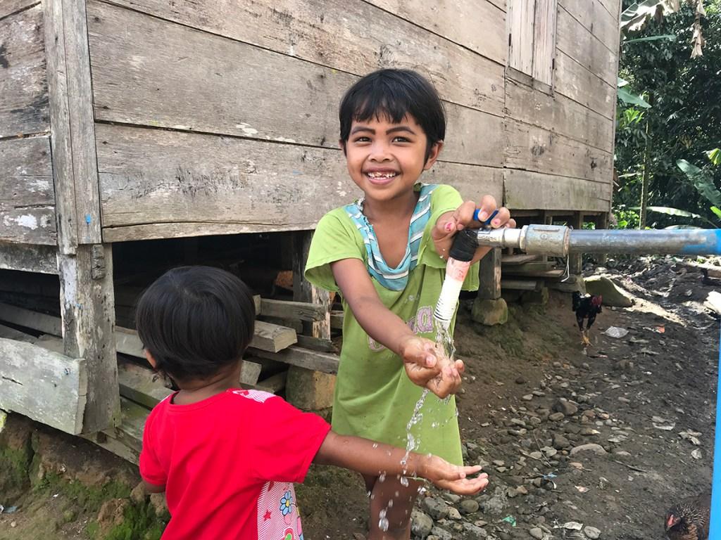 Children draw safe water in Indonesia.