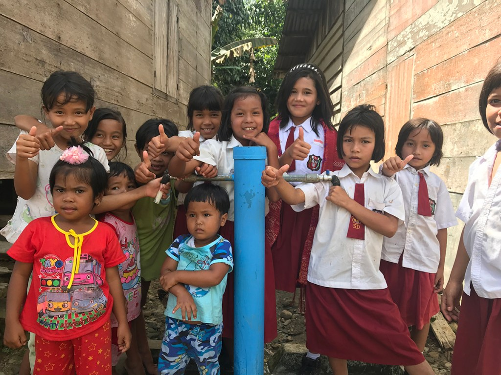Children stand by a safe water tap in Indonesia.