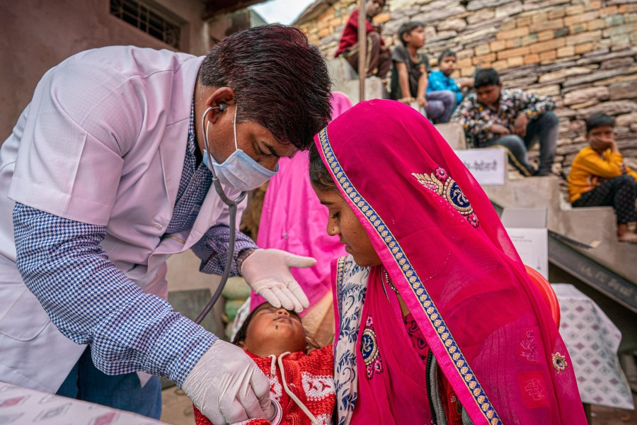 A mother holds her sick child as a doctor check's the child's vital signs.