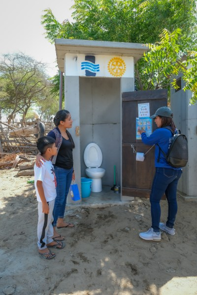 a woman shows a mother and child a Water Mission Healthy Latrine.