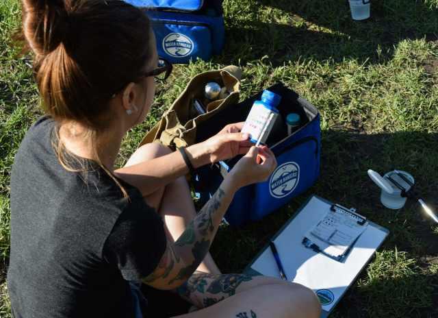 Une femme est assise sur l'herbe et lit une mesure de pH d'eau douce en comparant sa bande-tests à l'échelle sur la bouteille. Le pH est estimé en comparant le changement de couleur à l'échelle de référence.