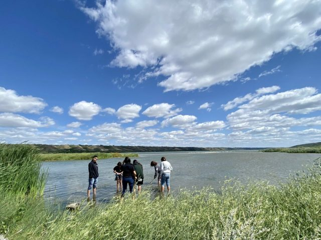 A group of youth are seen testing the water at an inlet of a River in Saskatchewan.
