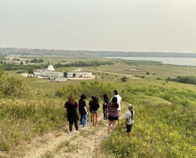 A group of camp attendees look out over the Treaty 4 Governance Centre and Qu'appelle Valley.