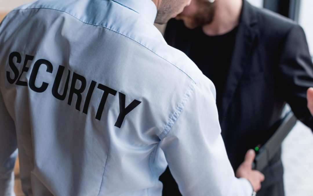 """This image is of two people, both who appear white and male. One person is wearing a light blue shirt that says """"Security"""" typed out across the back shoulderblades. That person is waving a metal detector wand over the second person who has their hands up and is wearing a black suit."""