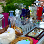 This is a photo of a various assortment of vases, jars, and glassware sitting on a card table outside with different priced sales tickets attached to each piece, presumably for a garage sale or estate sale.