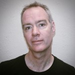 This is a head shot of the poet John Wall Barger. John is white and has gray and brown hair. He is wearing a black shirt and looking directly into the camera.