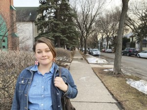 This is a photo of Halee Kirkwood. They are wearing a blue shirt and a blue demin jacket, carrying a brown bag. Halee is standing on a sidewalk. The grass is brown and some of it is covered with snow. The trees are bare. It appears to be late spring.