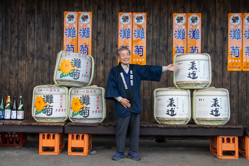 The CEO of the Nadagiku Brewery and their products in sake barrels.