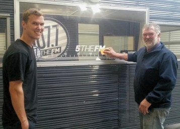 Tom and Dave Reilly putting the finishing touches to the window decal resembling a radio dial
