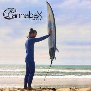 Male surfer holding surfboard in the air against the wind using eco-friendly surf wax.