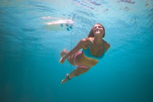 Female surfer swimming in bathing suit under water smiling.