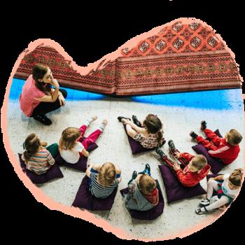 niños sentados al rededor de una mujer