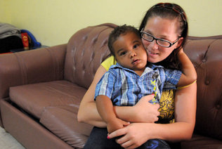 Ashley Maddox hugs her son, Miguel Romero III, who will be 2 in December, n her Little Havana apartment before leaving for work. [Photo: Marice Cohn Band/ Miami Herald Staff]