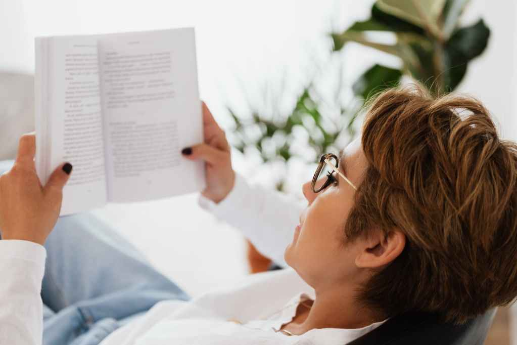 calm woman in eyeglasses relaxing with book