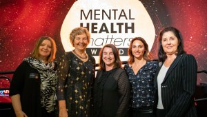 Jewish Care staff staning in front of the Mental health Matters logo