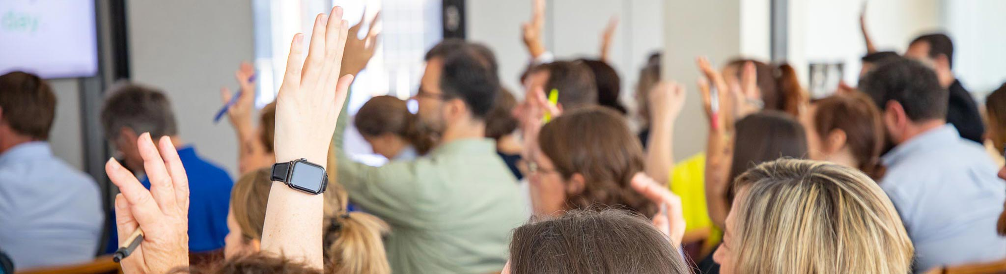 Participants at a WayAhead Workplaces meeting raising their hands in response to the speaker