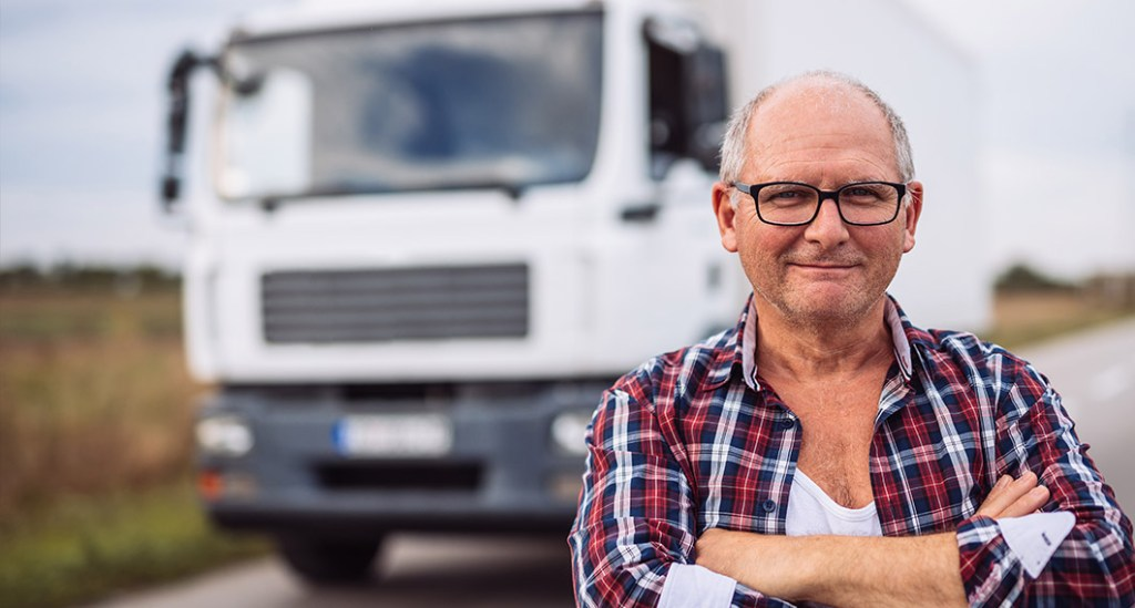 Older man standing in front of a truck