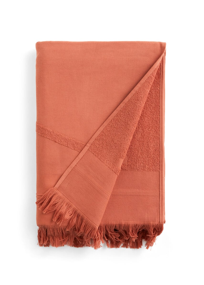 Folded red WAY beach towel with woven front and terry back and fringes