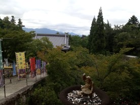 view from the temple, stairs and tons of greenery and in the foreground a small statue sitting in what looks like a bird bath full of money