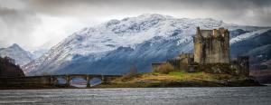 A castle in Scotland on an island with an old stone bridge to the left leading towards a wooded mainland with snow covered mountains in the background and water in the foreground.