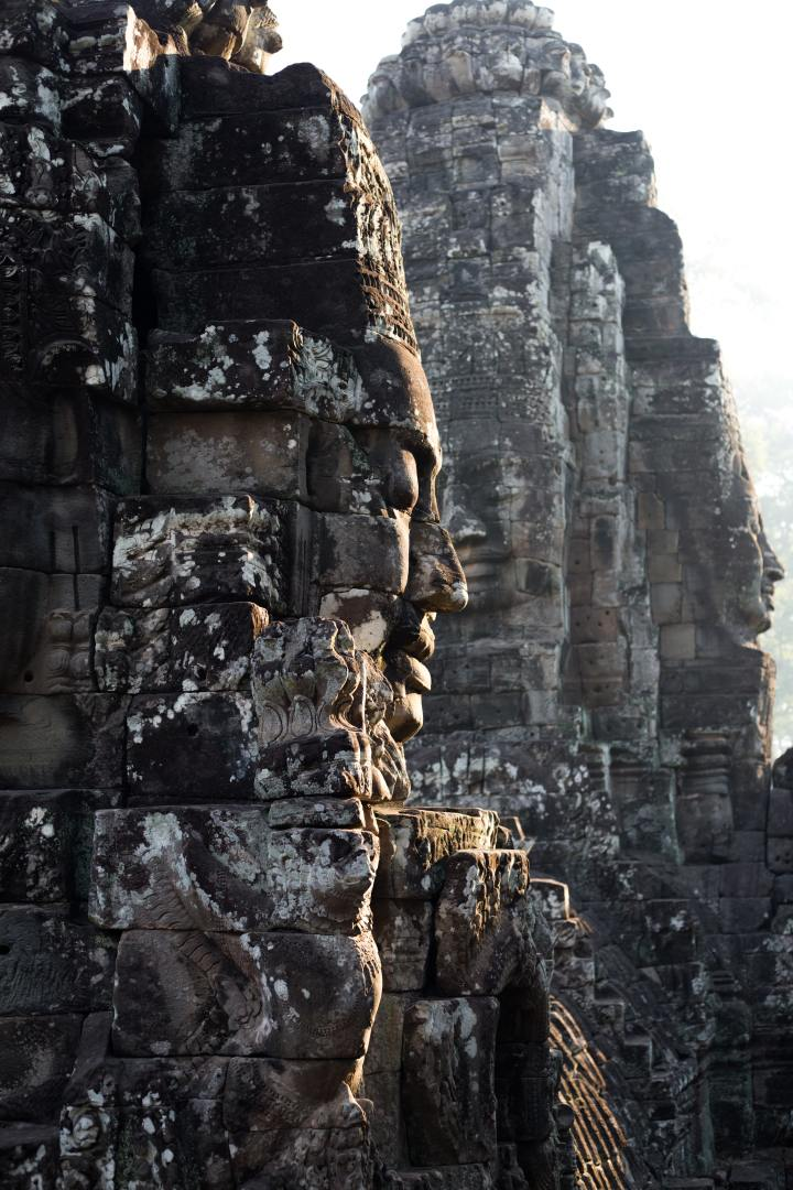 A large profile face put together in old blocks of stone in the foreground with more in the background facing at different angles. The stones are old and discolored in spots, darker in areas and with a whiter look in other areas. Taken according to the photographer at Bayon Temple, Krong Siem Reap, Cambodia.