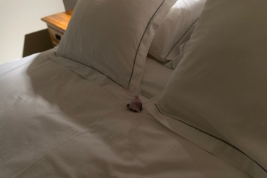 Sweet chocolates on the bed at night.
