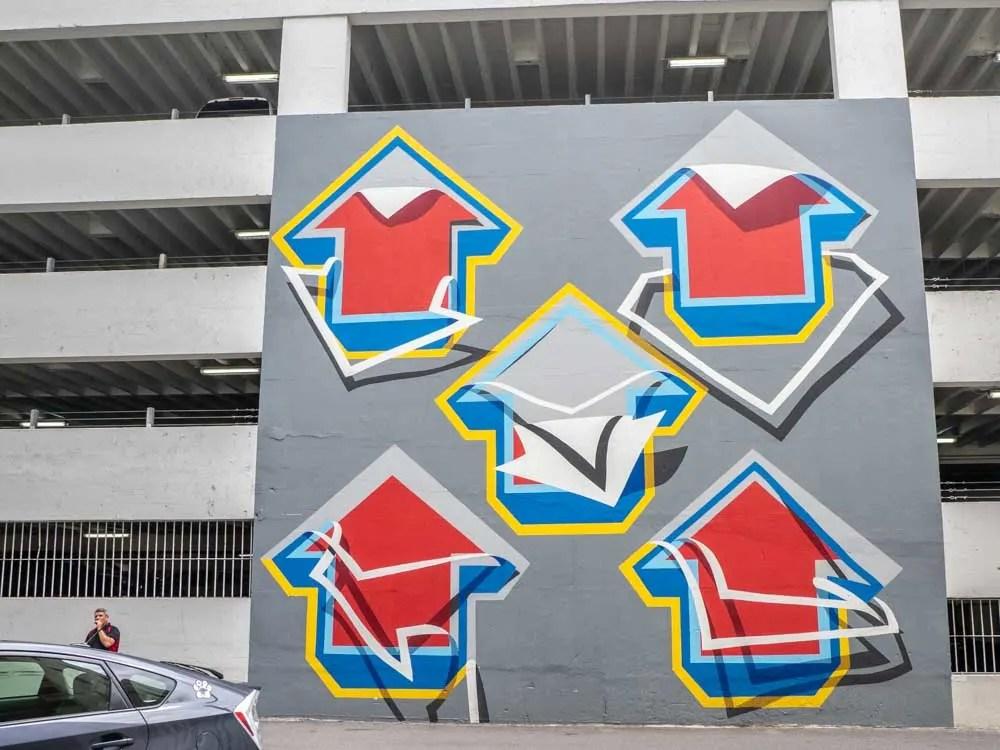 Mural Tavar Zawacki on parking lot wall- red and blue arrows