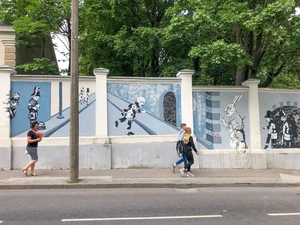 Tartu children's story mural by Hare. blue street art with people walking on sidewalk.