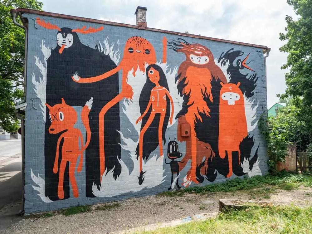 Tartu street art mural by KZRTE. black and orange folk characters