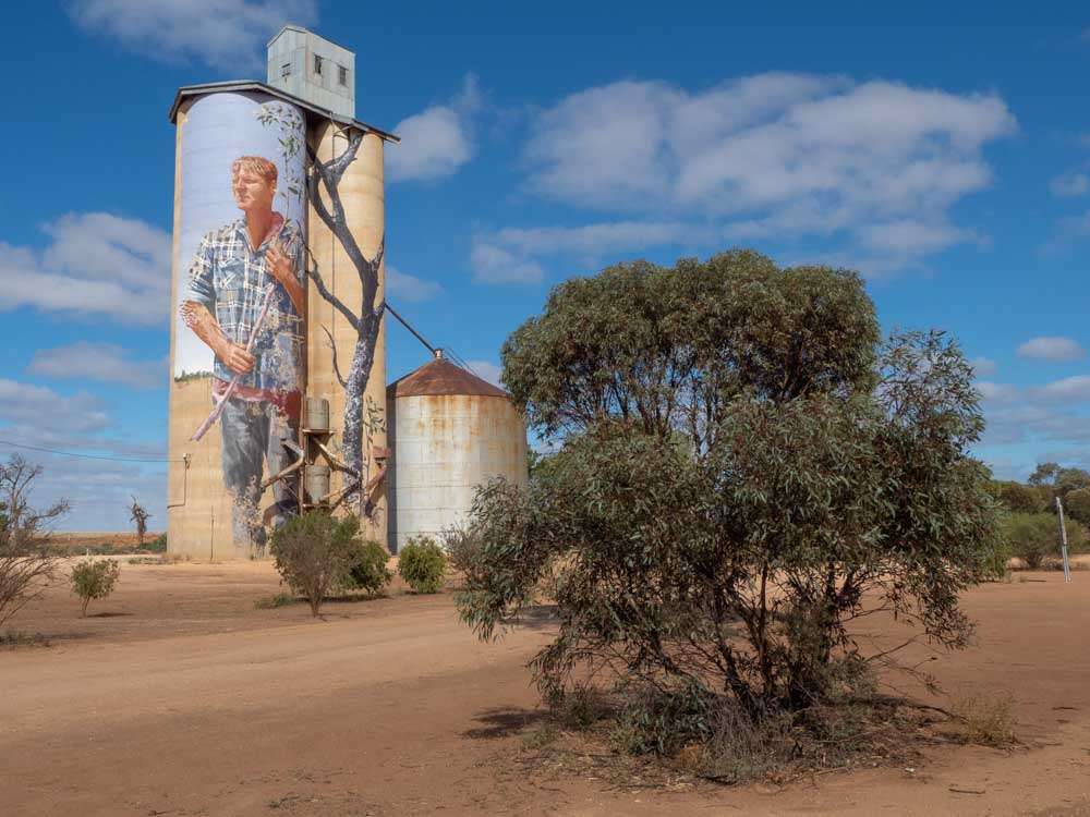 Painted silos of Victoria Australia, FIntan Magee mural of a farmer with a bush