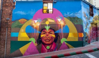 Bogota Graffiti tour Guache mural of an Indigenous person with blue, green and pink colors