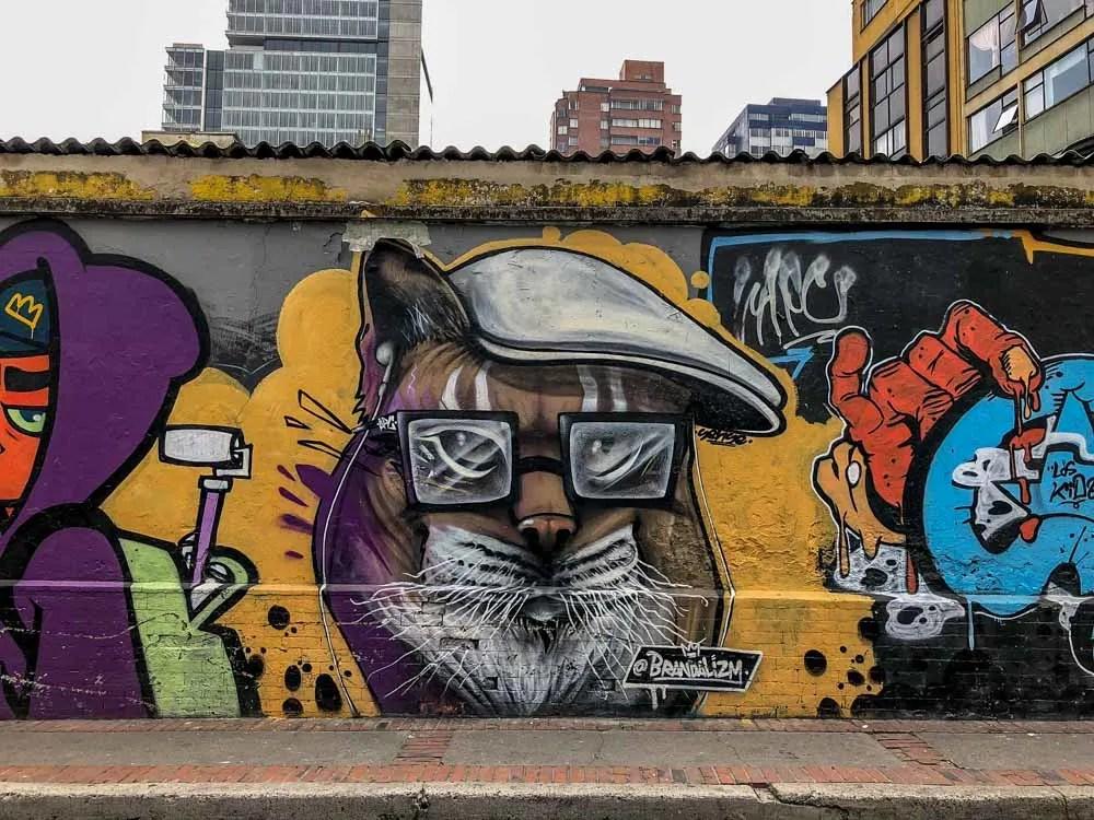 Bogota street art cat by Brandalism. Multicolored cat wearing a hat