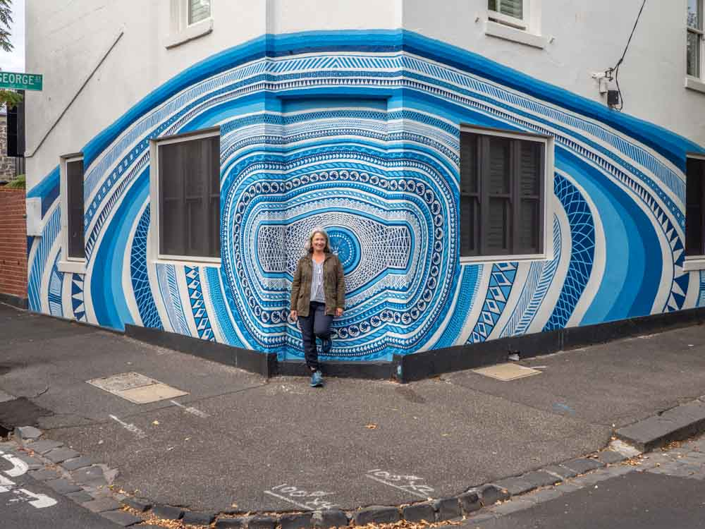 Mural in Melbourne's Fitzroy. blue painting with woman standing in front