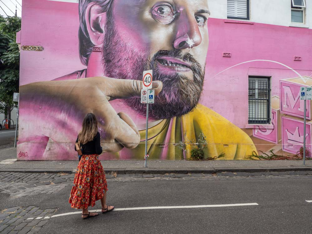 Melbourne mural in Fitzroy by Smug. Man with yellow shirt and pink background.