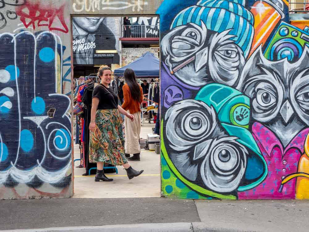 Graffiti in Fitzroy Market with woman in doorway